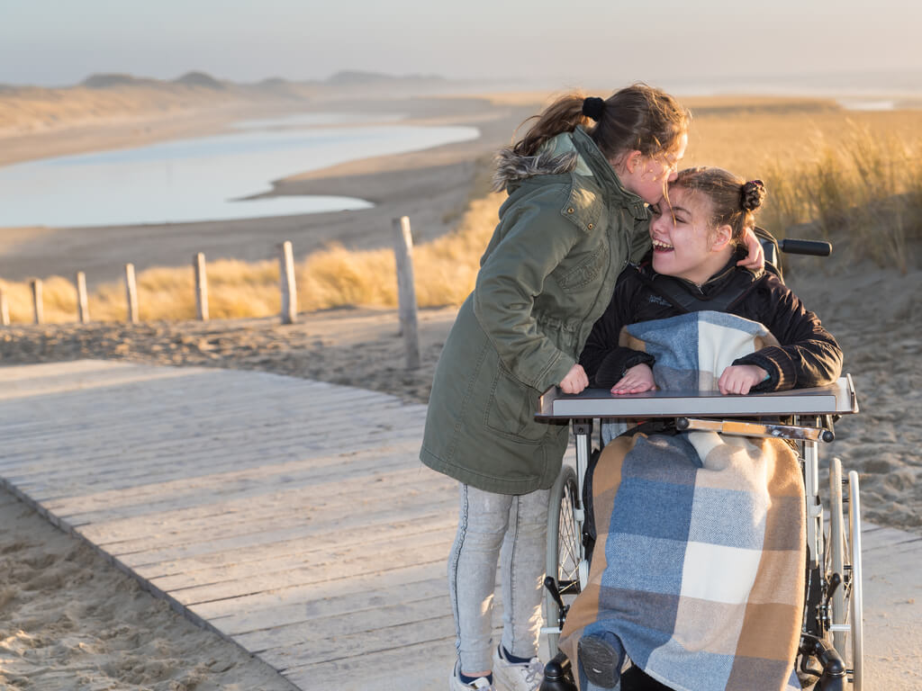 A young girl kisses the head of her sister who is in a wheelchair on a boardwalk