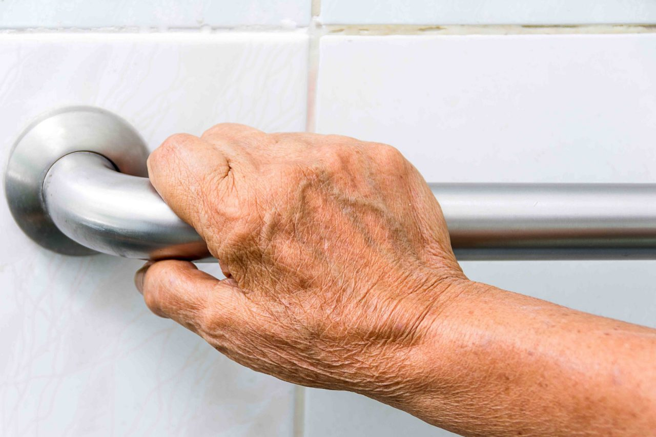 elderly holding a grab bar in an ada bathroom