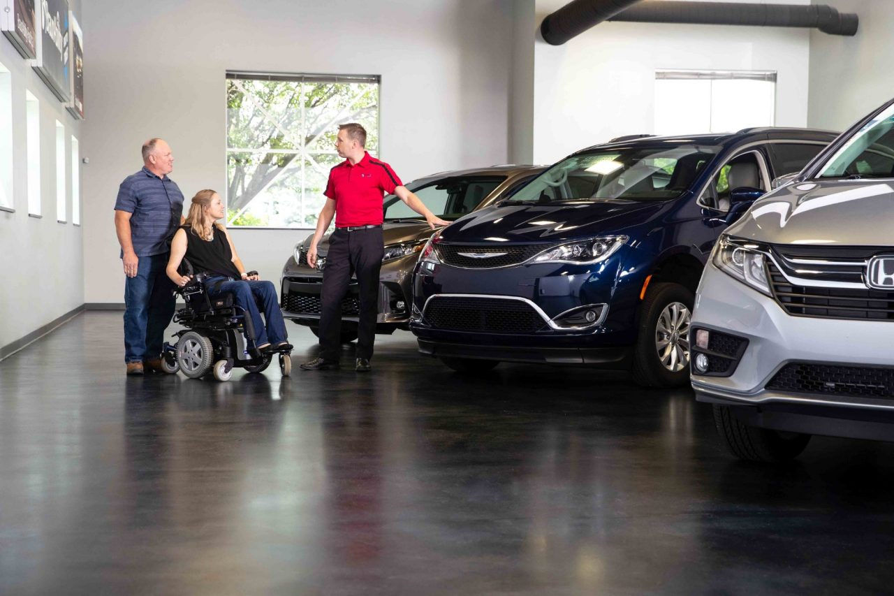Couple speaks to a dealer in a vehicle showroom about accessible vehicle