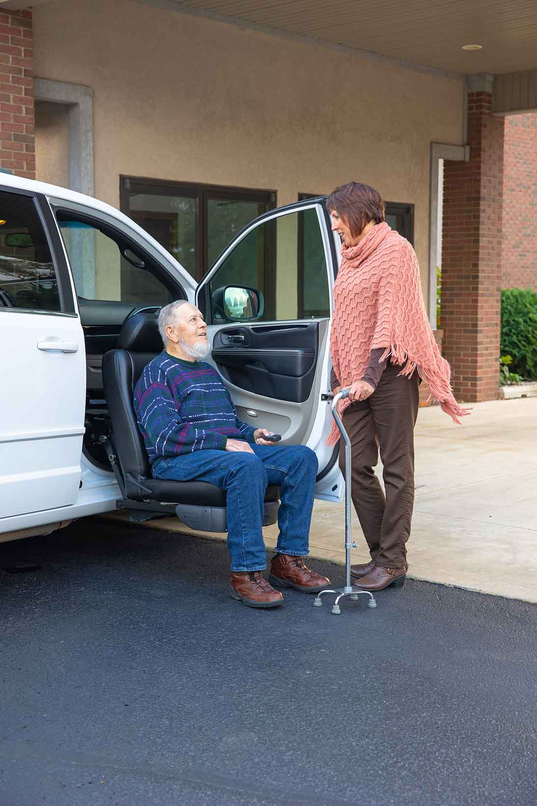 Mother and daughter using a rotating seat wheelchair lift in a dodge minivan