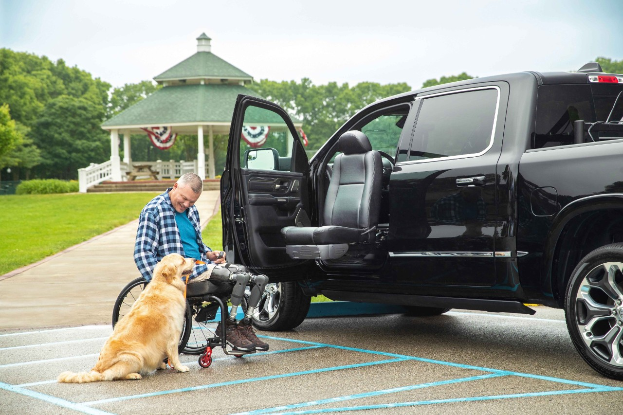 A veteran an d his dog by the Turny Evo Seat for a  truck wheel chair lift.