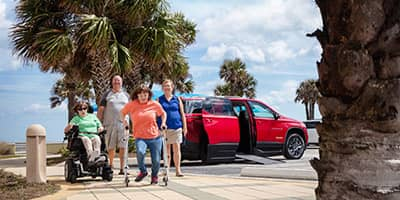 a family with a red chevy traverse wheelchair conversion truck