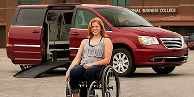 girl in a wheelchair in front of her Chrysler Town and Country handicapvan mobility vehicle