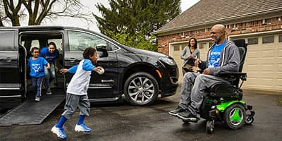 A family with a BraunAbility Chrysler Pacifica Mobility Vehcile in a driveway