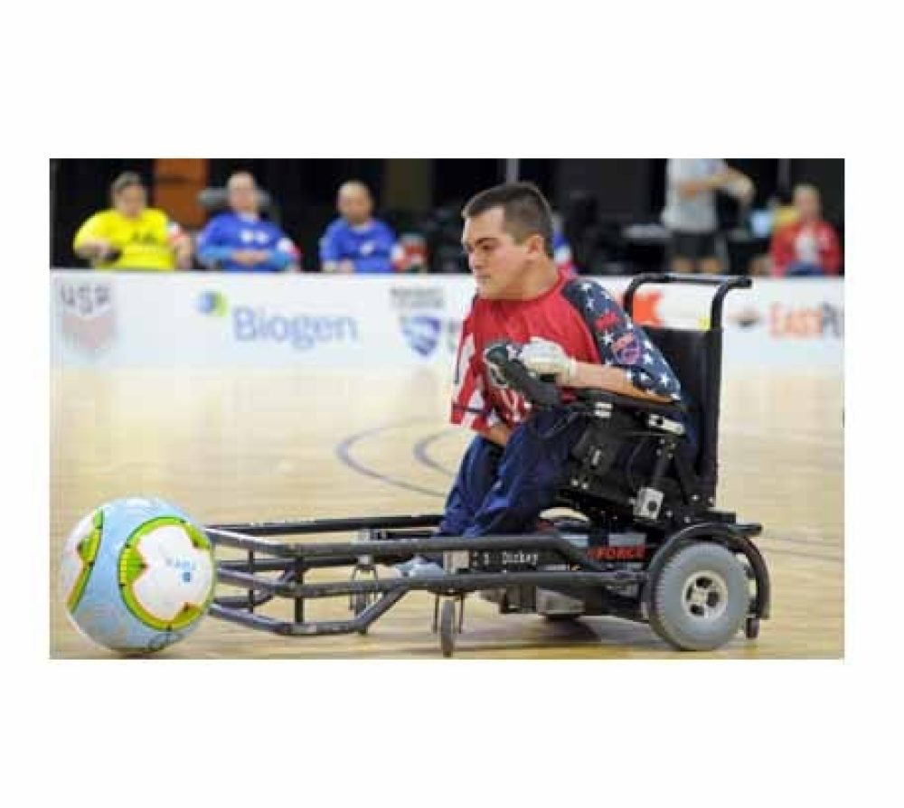 A young boy playing the sport of power soccer