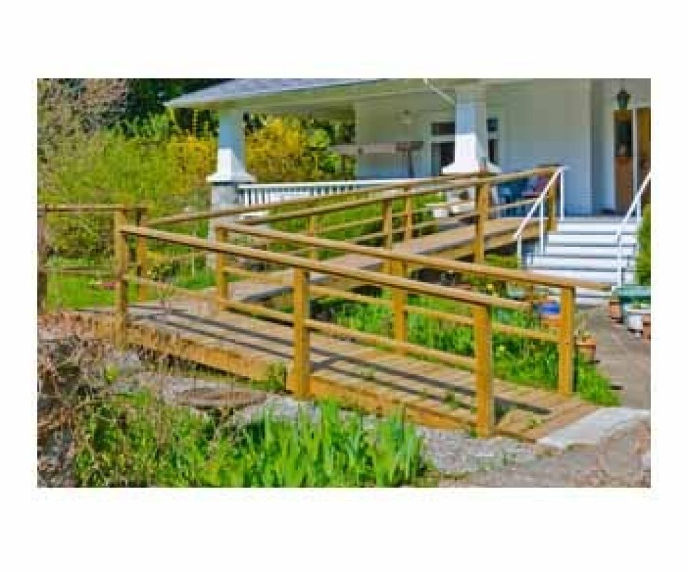 wood wheelchair ramp for house on a white house with green grass