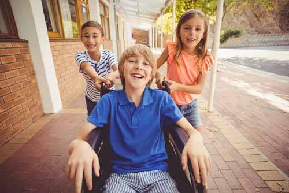 a young boy wearing a blue shirt in a wheelchair is being pushed by 2 girls who are is friend