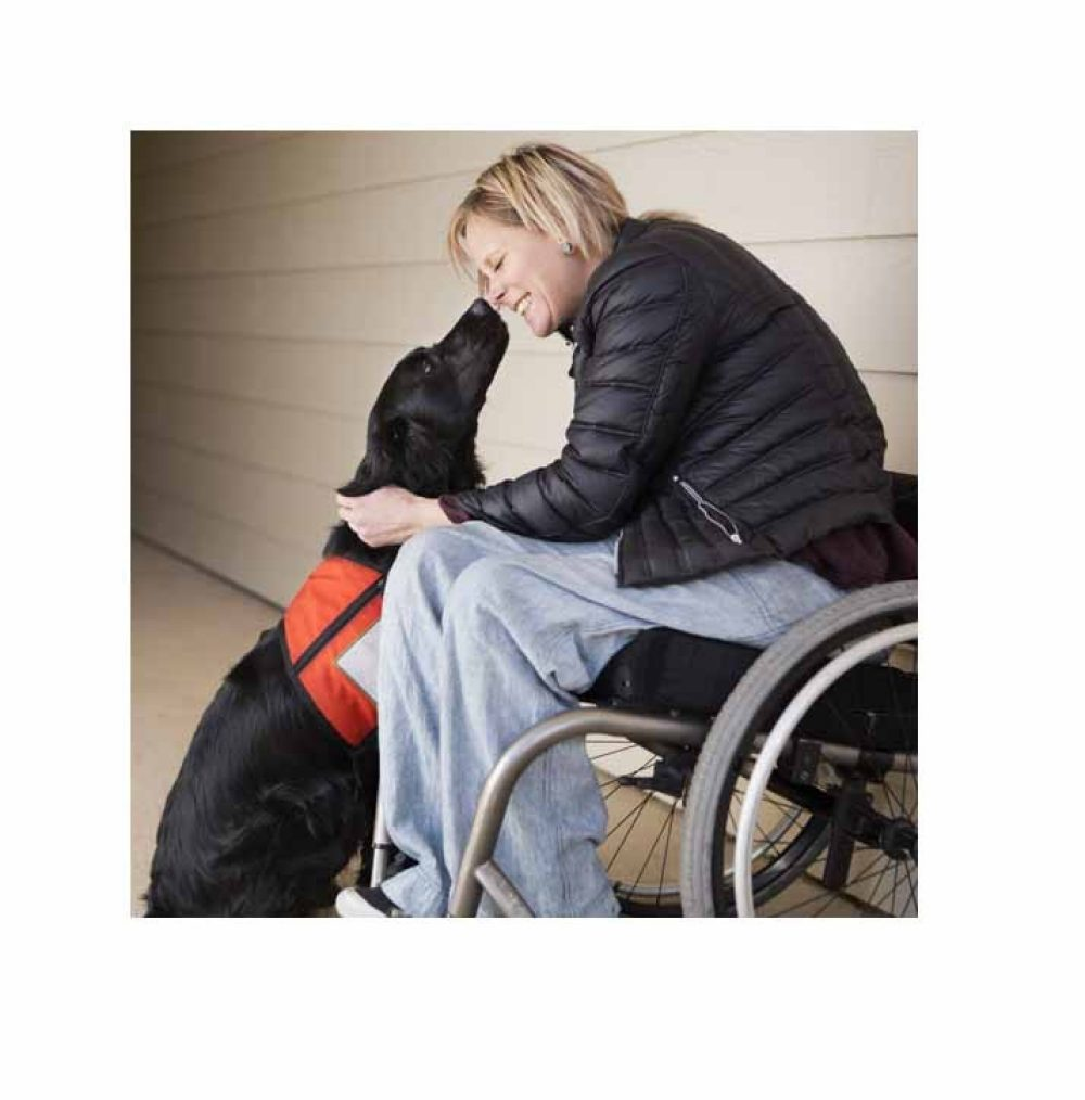 A girl sitting in a wheelchair with her service dog