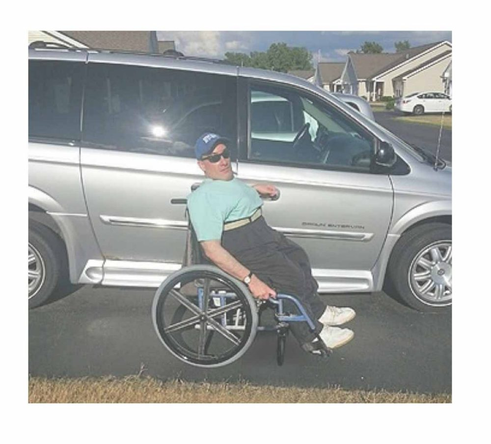 Tom Turner poses in front of his BraunAbility Entervan|Tom Turner, a longtime BraunAbility customer, at the racetrack