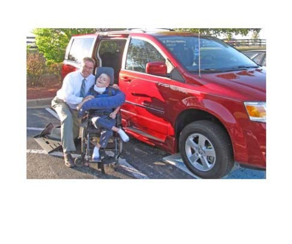 2 people sitting in front of a red wheelchair van with wheelchair ramp
