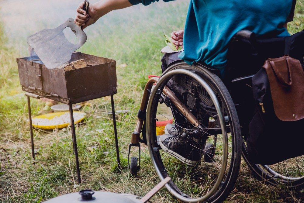 person in a wheelchair grilling food while camping