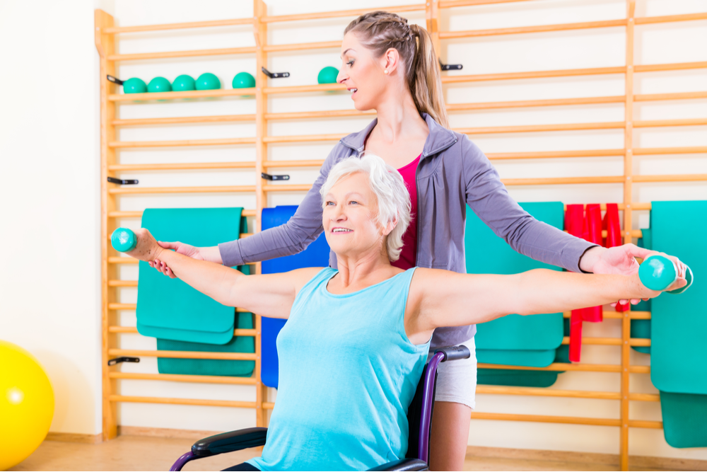 Elderly woman in a wheelchair holds free weights at her side with the help of a female trainer