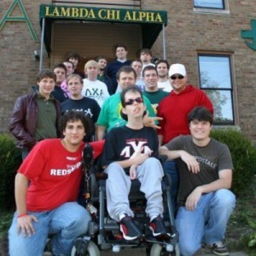 A group of college-aged men, including one in a wheelchair, pose in front of a house they share together