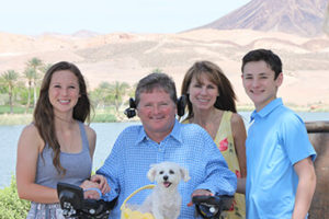 Sam Schmidt poses for a picture with his wife, two kids, and dog