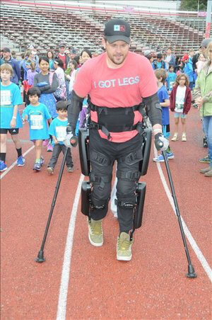Adam, founder of I GOT LEGS, shows off his exoskeleton which he got by fundraising for mobility equipment