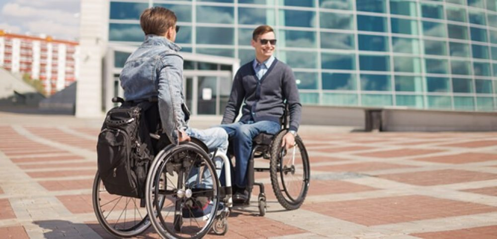 Two men in manual wheelchairs stop to talk outside of an office building