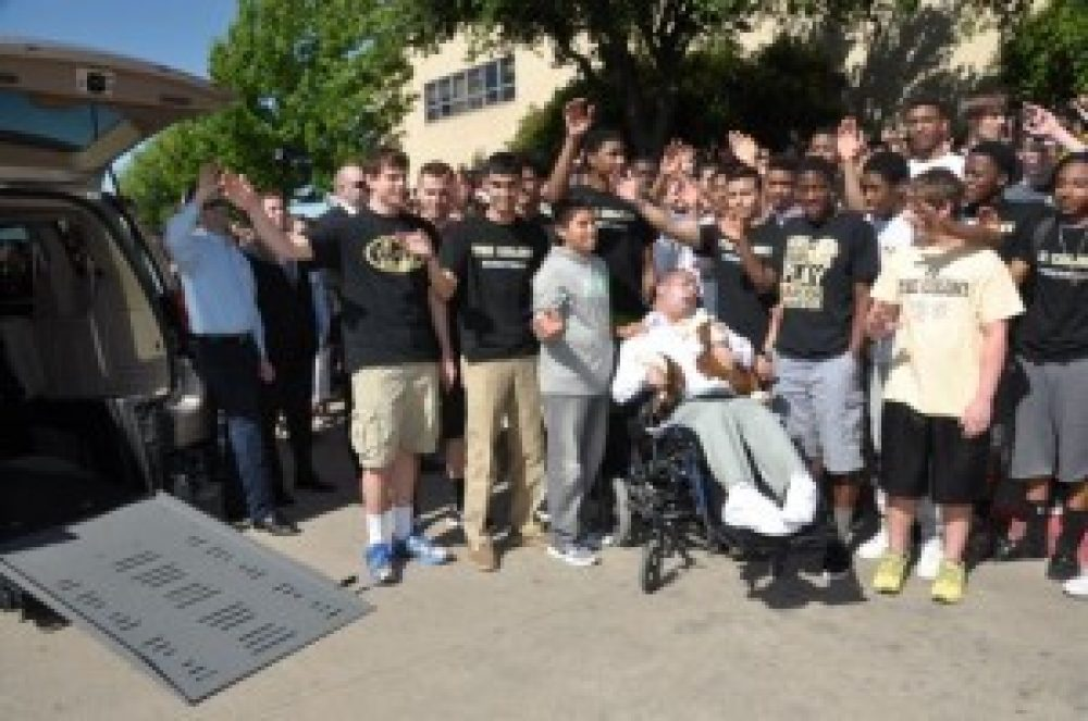 Colony High School students gather around Brian in a power wheelchair and wave