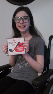 Haleigh McKee holds her Songs of Love CD written especially for her.