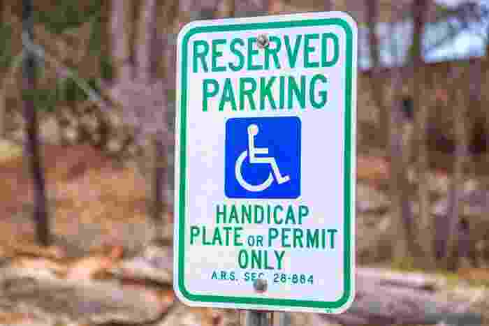 A sign for handicap parking indicates the need to have a handicap parking permit to avoid a fine|A man in a wheelchair sits next to a vehicle with the driver's door ajar illustrating a handicap parking permit requirement|A blue handicap parking permit hangs from a rear-view mirror