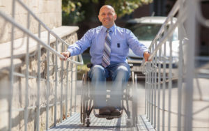 A hispanic man in a wheelchair poses at the end of a wheelchair ramp