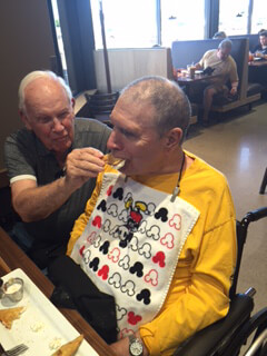 BraunAbility customer story: Kenny's cousin Roy feeds him during a dinner outing