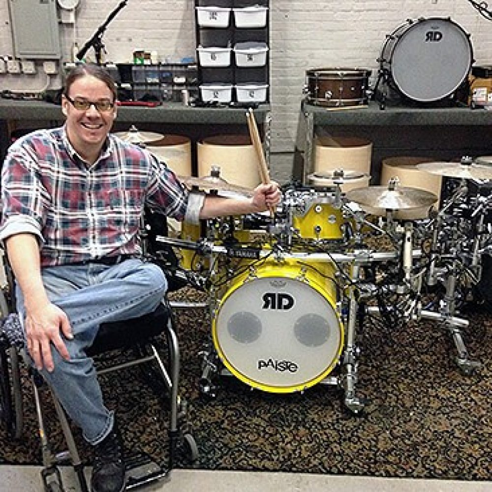Jason Gerling sits in his wheelchair and poses with his modified drum kit