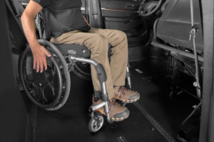 A man in a manual wheelchair illustrates the space-saving design of BraunAbility Tilt N'Go seats on the BraunAbility MXV, a wheelchair accessible SUV.