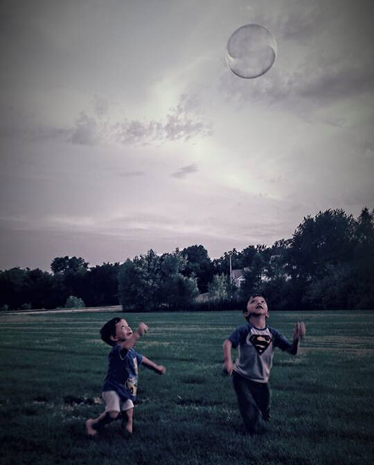 Two boys with a rare disease chase bubbles in a field
