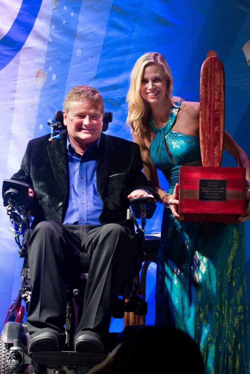 Sam Schmidt and a representative from Life Rolls On holds the Freedom Award