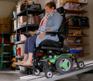 An older woman exits her home to a garage in a power chair via an aluminum portable ramp system.
