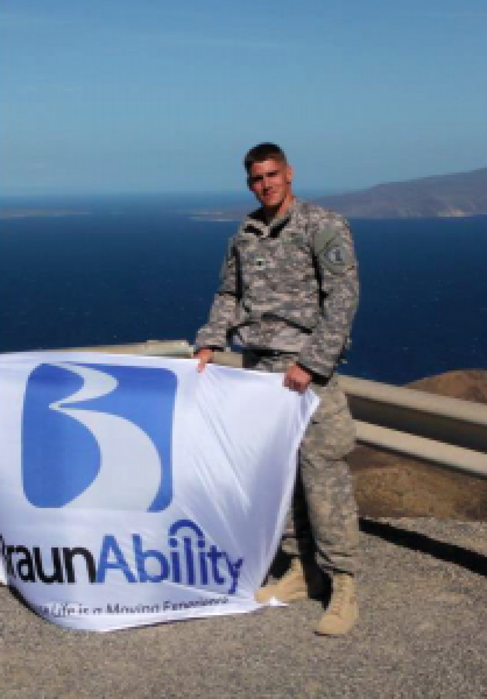 Sergent Don Perkins holds a BraunAbility flag while stationed at his deployment location