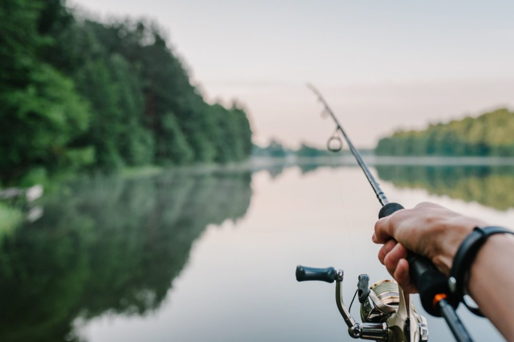 A hand holds a fishing rod facing a quiet, serene lake