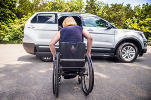 A woman in a manual wheelchair approaches a BraunAbility MXV