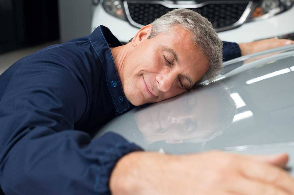 Man hugs the hood of his car with his eyes closed