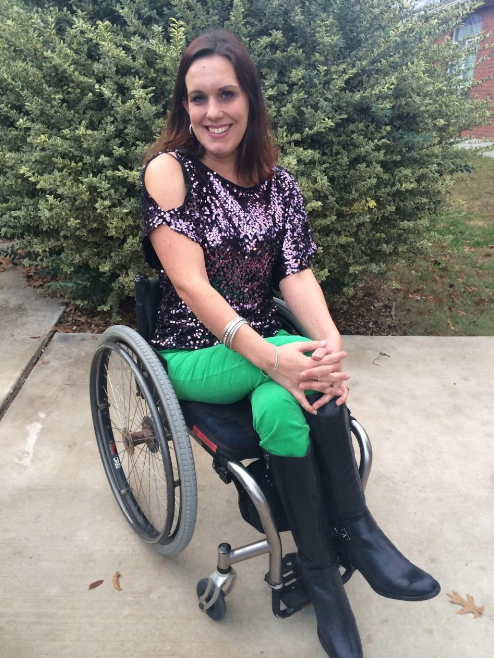 Priscilla Hedlin is wearing a sparkly purple shirt, green pants and black leather boots