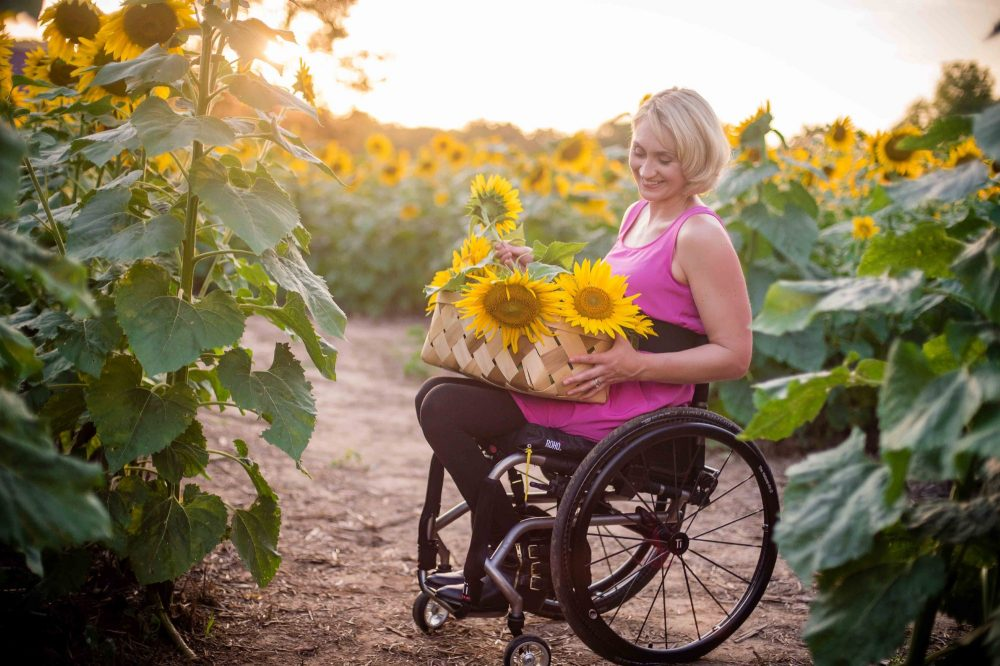 Woman in a wheelchair in a sunflower field with a basket of flowers on her lap