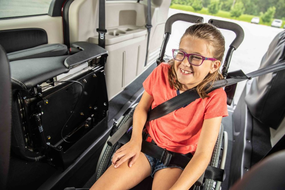 A young girl smiles while secured in a wheelchair in a rear-entry accessible vehicle