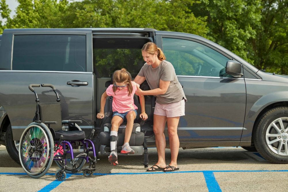 mom helping her young daughter transfer from her manual wheelchair to a Transfer Seat installed on a handicap van