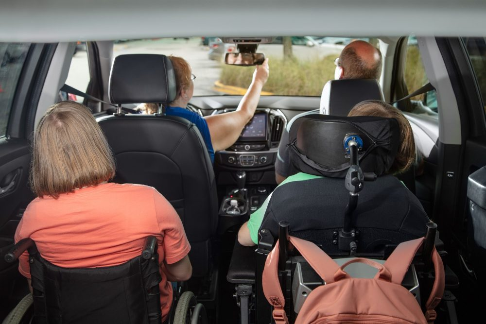 2 girls in wheelchairs ride in a Chevy traverse wheelchair SUV with their parents