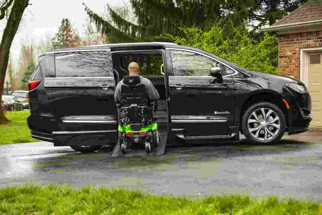 man using infloor wheelchair ramp on Chrysler pacifica handicap van