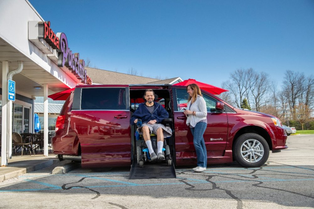 Man exits a BraunAbility side-entry Dodge van in a power chair while his wife stands to the side