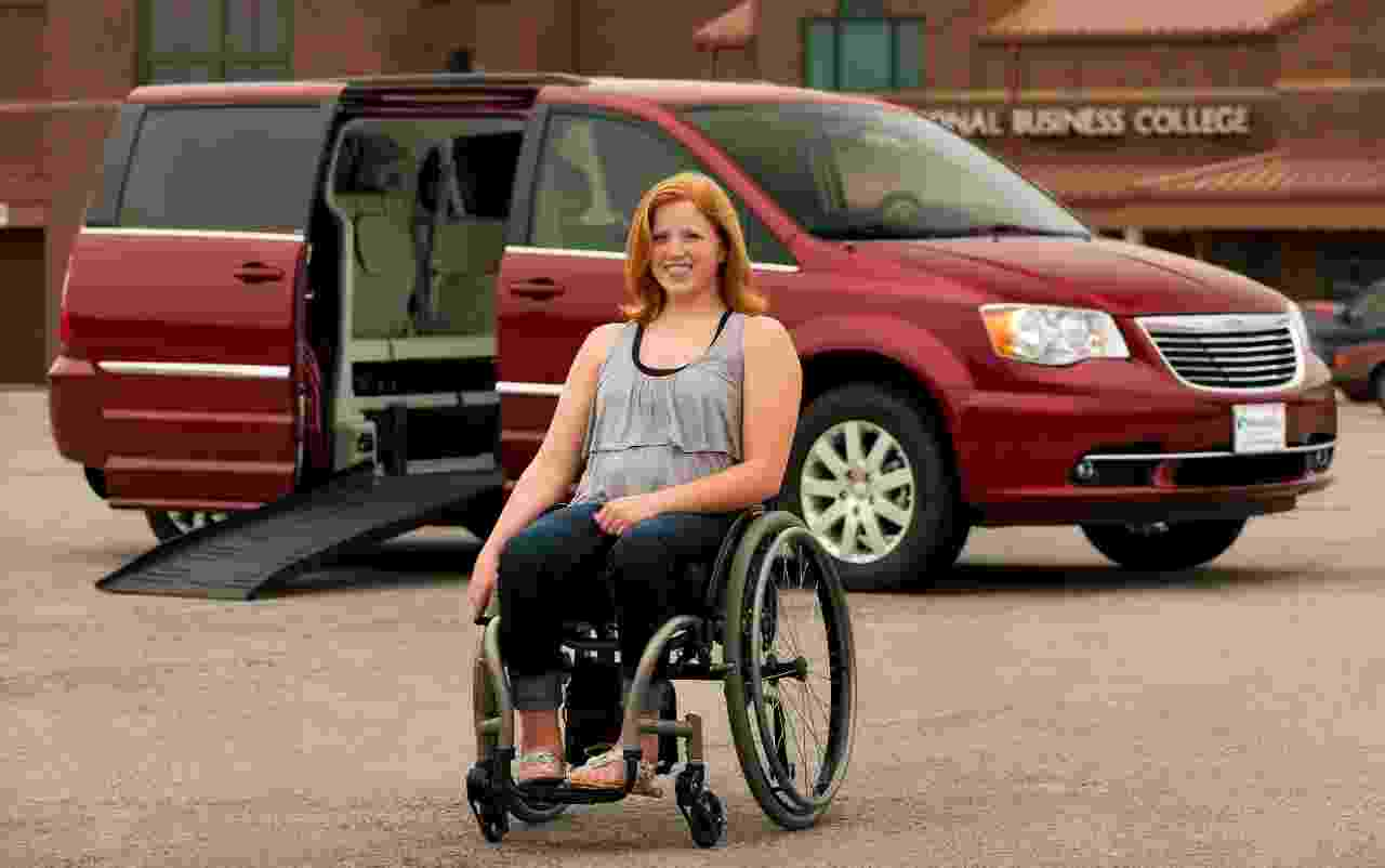 girl in front of her Chrysler Town and Country handicap van