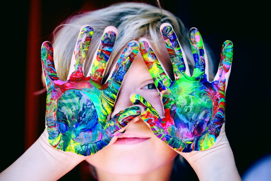 a child with many paint colors on the hands