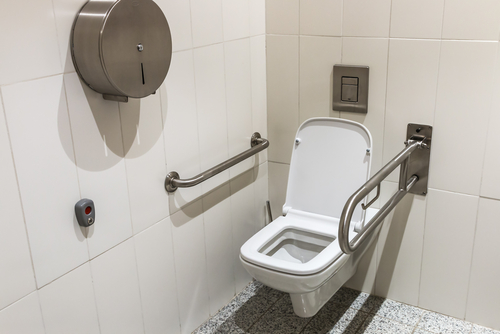toilet with handrails for the disabled. Focus on the lid of the toilet