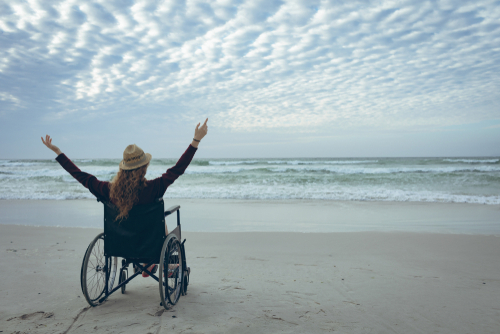 Rear view of young disabled Caucasian woman sitting with arms in the air in wheelchair facing the sea at beach. She wears hat