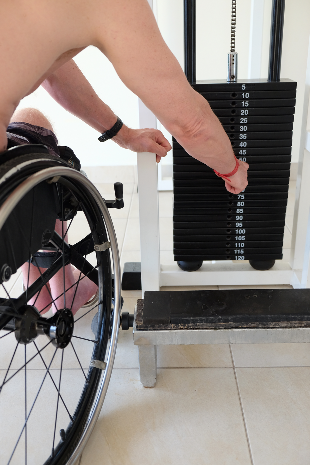 Man in a wheelchair adjusts his weight on a piece of workout equipment