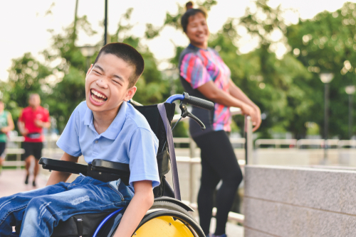 a mother and son at a park. The son is using a wheelchair rental