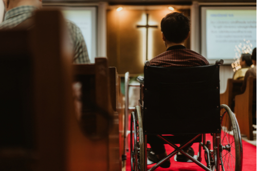 Man in wheelchair sits in the aisleway of a church during a service