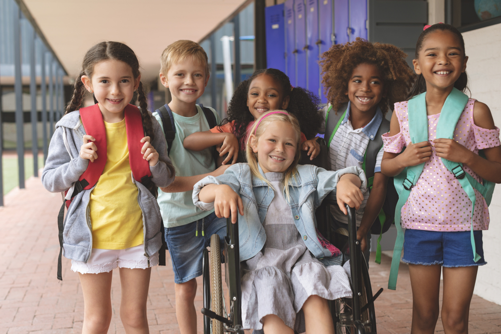 Front view of happy diverse school kids standing in outside corridor at school while a Caucasian schoolgirl is sitting on wheelchair in foreground