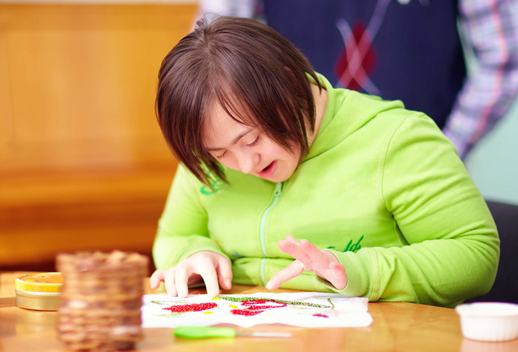 Girl with down syndrome works on a finger painting